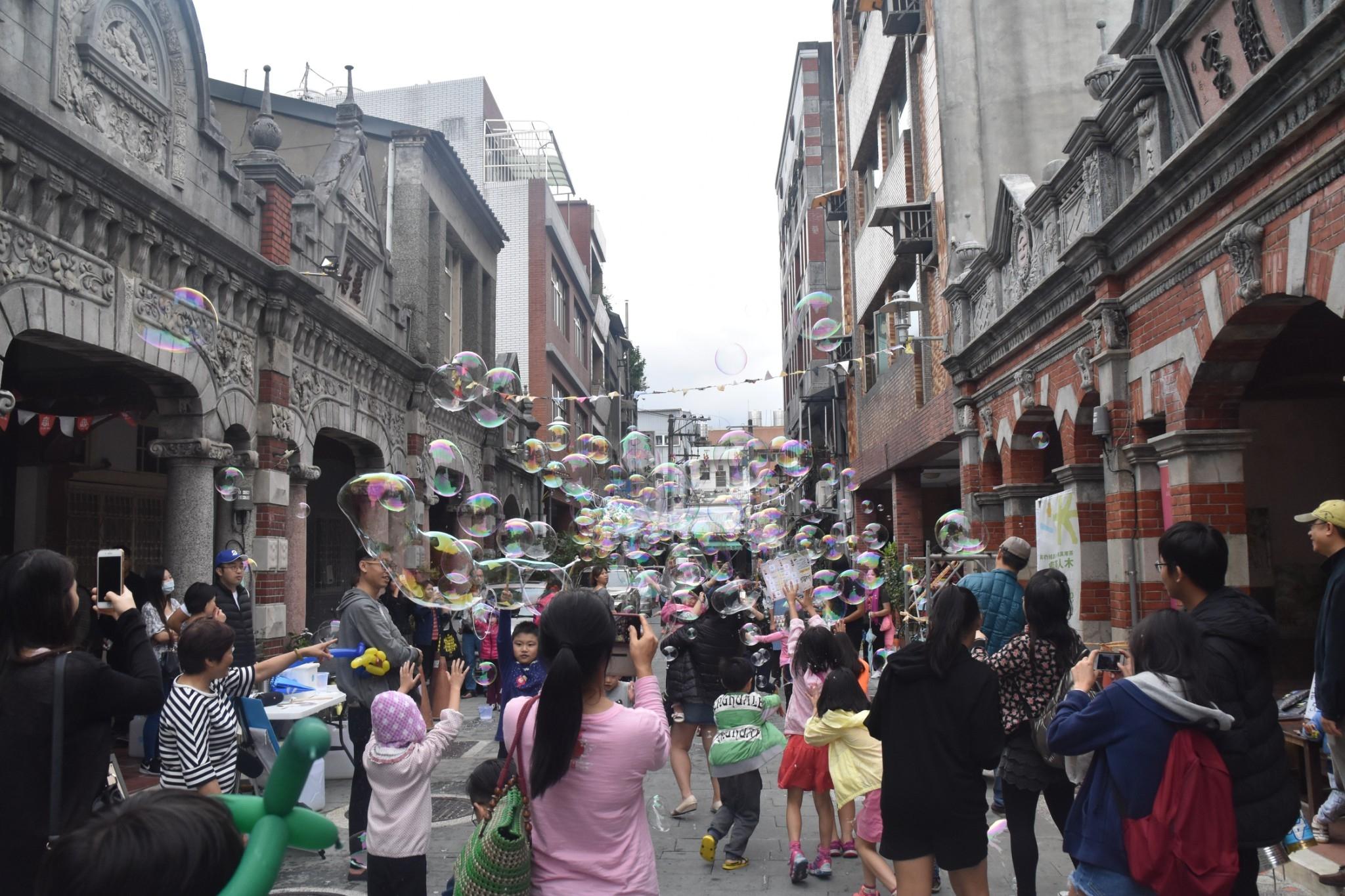 在老街上吹泡泡頗有懷舊童趣