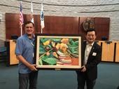 秘書處處長顏子傑代表市長致贈桃園原住民畫家米路.哈勇「水蜜桃之戀」予爾灣市長Donald Wapner