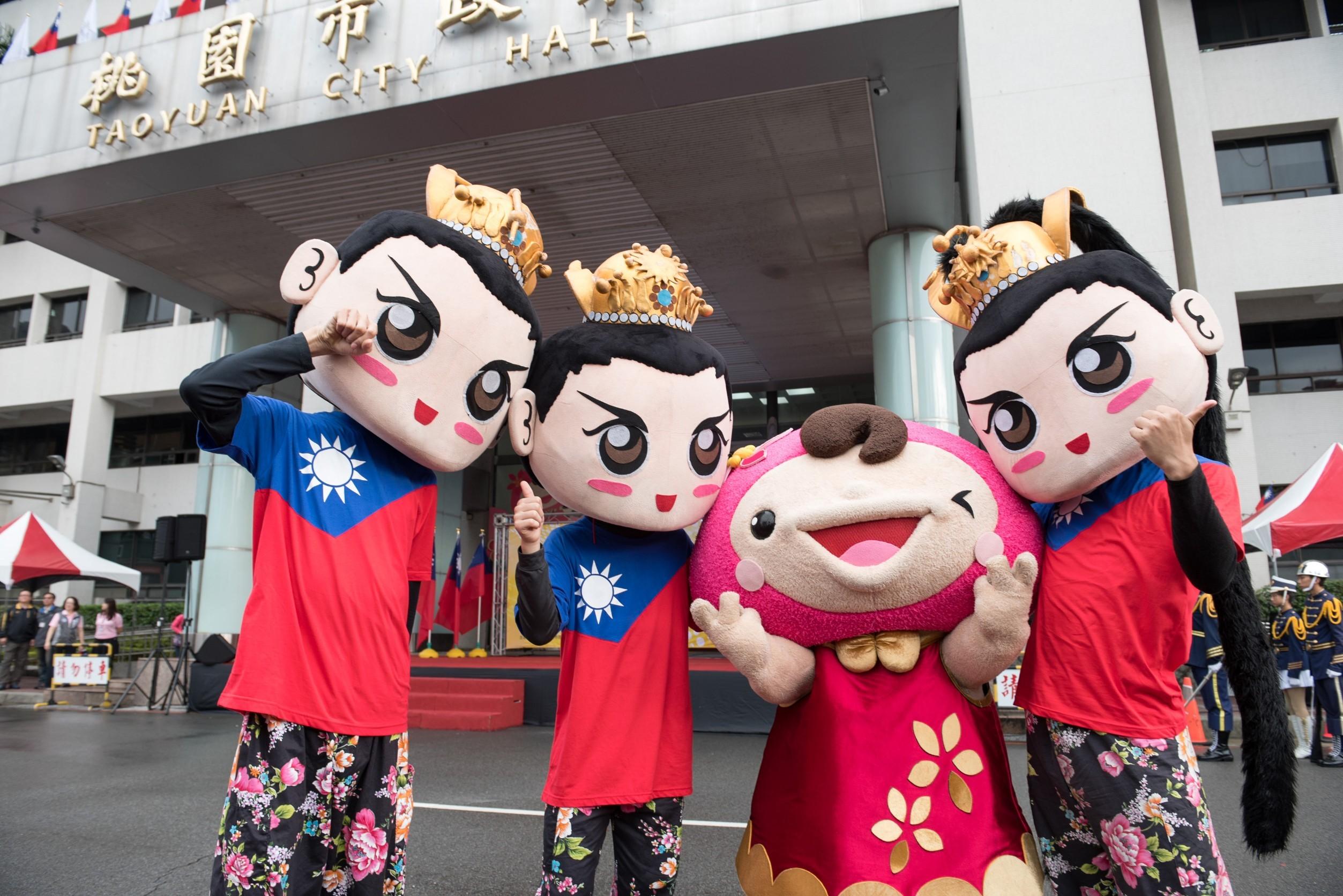 市府吉祥物ㄚ桃和著國旗裝、戴人偶頭像的表演者合影