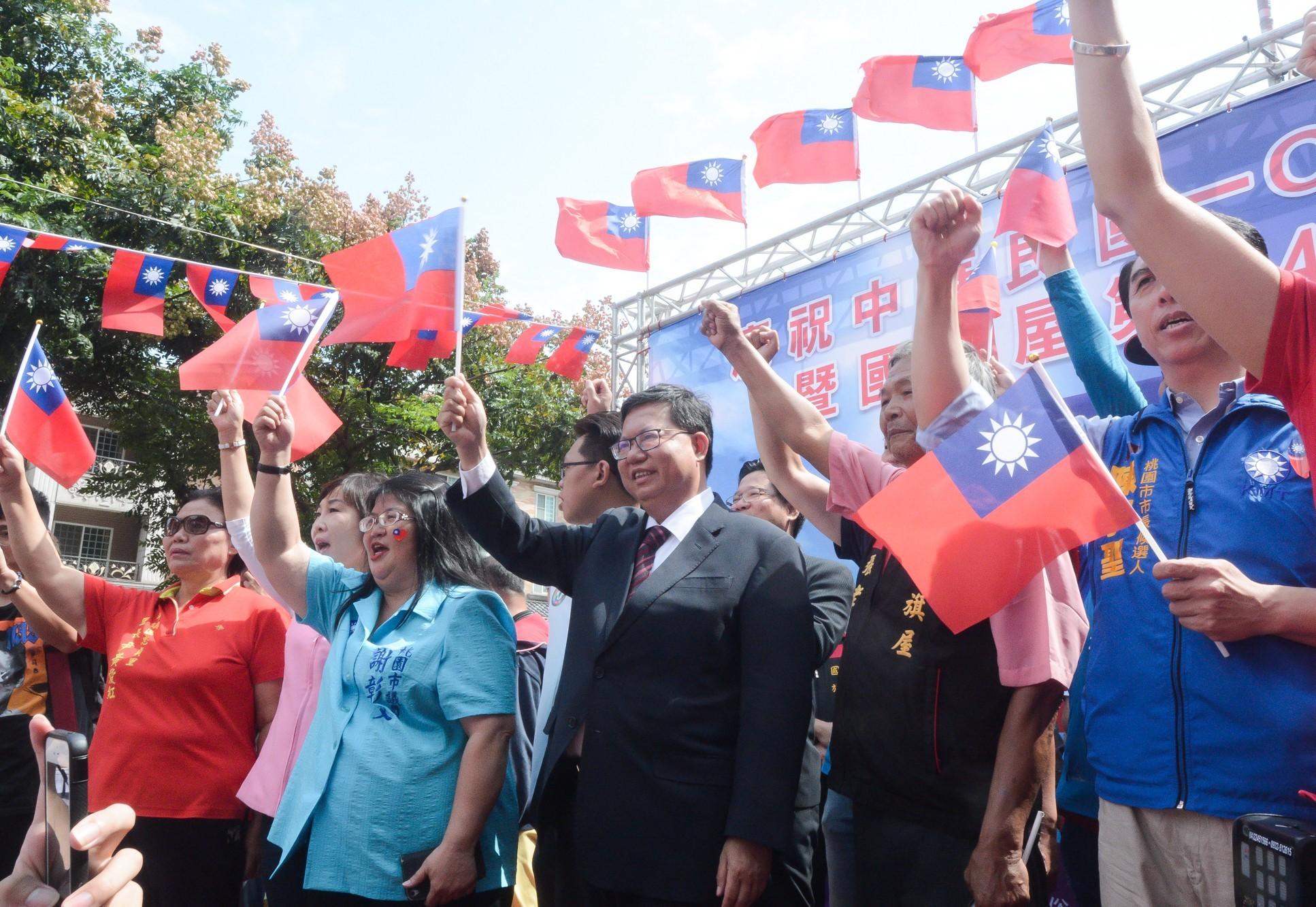 市長和與會來賓一起高舉國旗,慶祝國家生日快樂