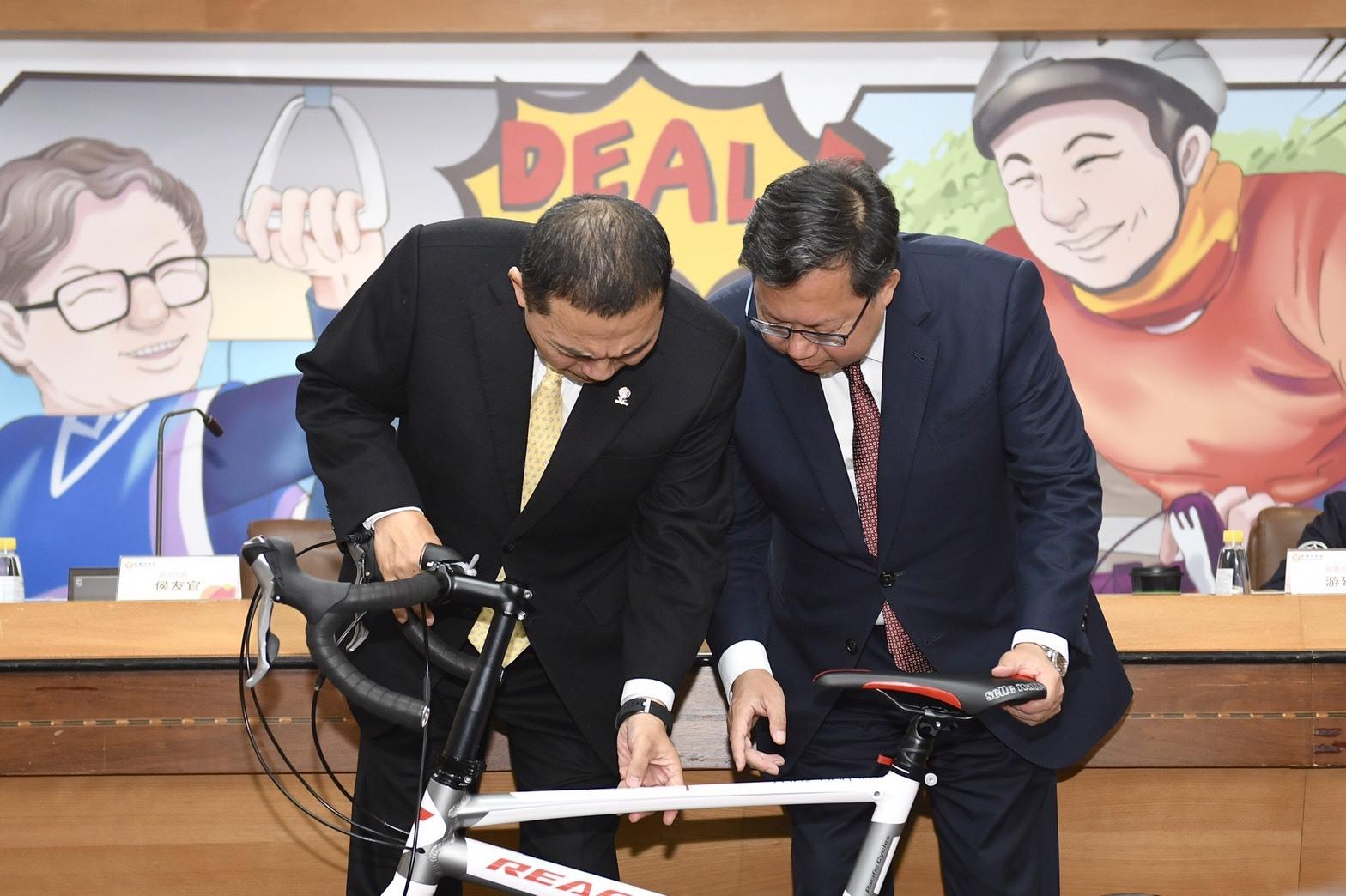 鄭市長向新北市長侯友宜說明致贈「太平洋公路自行車」涵義以及設計巧思