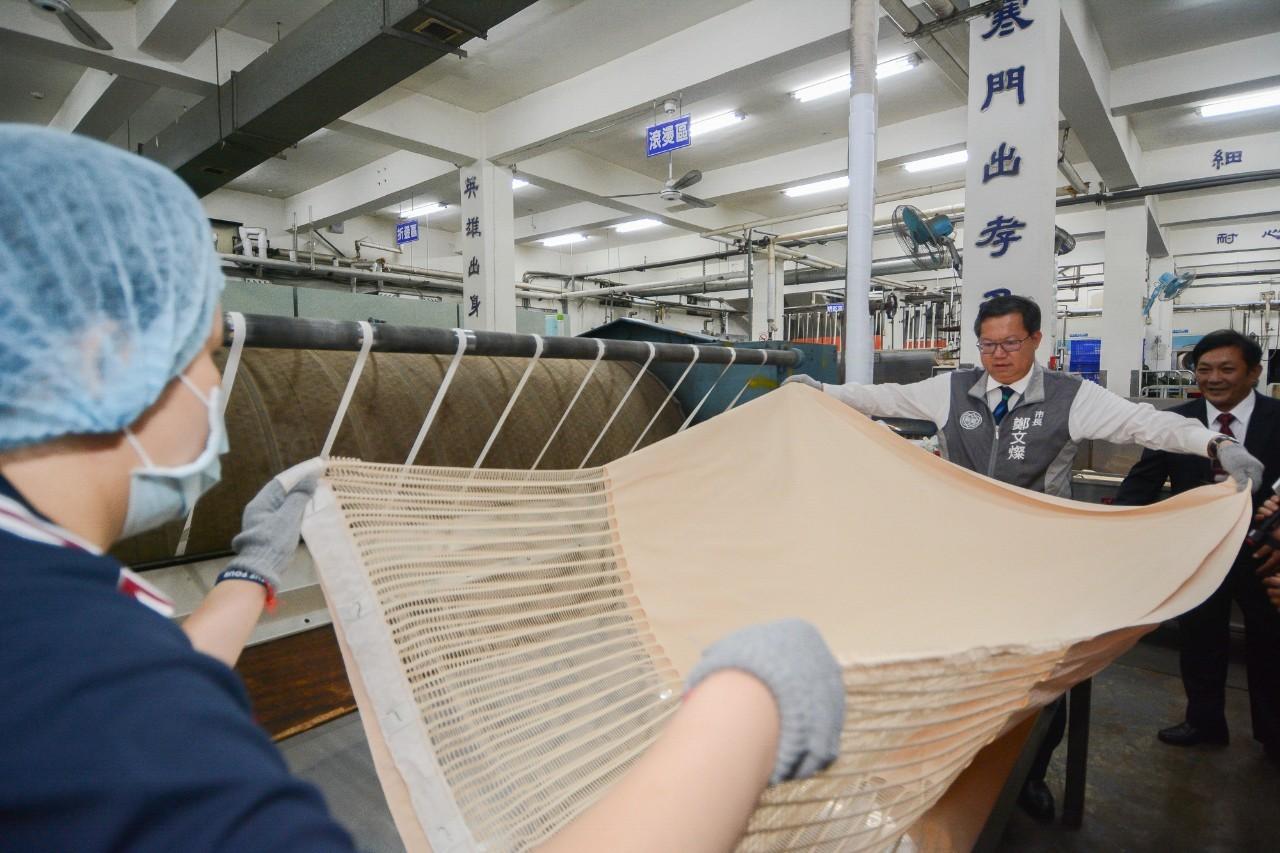 市長與員工一同攤開織物